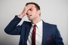 Attractive business man holding head like hurting. On gray background Royalty Free Stock Photography
