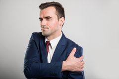 Attractive business man holding shoulder like hurting. On gray background Stock Photos
