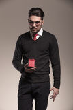 Attractive business man holding a small red gift Royalty Free Stock Images