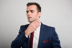 Attractive business man holding throat like hurting. On gray background Royalty Free Stock Photos