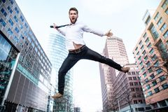 Attractive business man is jumping in the air stock photography