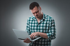 Attractive business man model in green shirt  on gray working with laptop, showing something by left hand. Royalty Free Stock Images