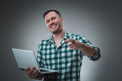 Attractive business man model in green shirt  on gray working with laptop, showing something by left hand. Royalty Free Stock Image