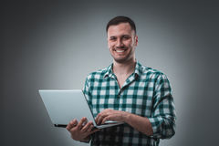 Attractive business man model in green shirt  on gray working with laptop, showing something by left hand. Stock Images