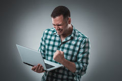 Attractive business man model in green shirt  on gray working with laptop, showing something by left hand. Stock Image