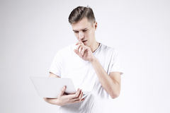 Attractive business man model in white t-shirt isolated on white working with laptop in right hand. Thinking about start-up projec Royalty Free Stock Image
