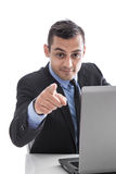 Attractive business man pointing finger at camera with laptop is Royalty Free Stock Images