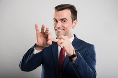 Attractive business man showing finger in whole gesture. On gray background Royalty Free Stock Images
