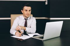 Attractive business man in smart casual wear sitting at his working place in office royalty free stock image