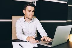 Attractive business man in smart casual wear sitting at his working place in office Stock Photo