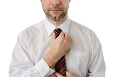 Attractive business man straightens his tie Stock Photography