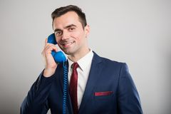 Attractive business man talking at blue telephone receiver. On gray background with copyspace advertising area Royalty Free Stock Photos