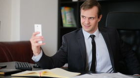 Attractive business man talking on the phone doing selfie at the office stock video