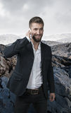 Attractive business man telephoned in a stone desert.  Royalty Free Stock Photos