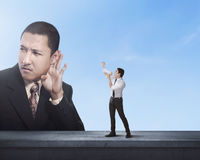Attractive business man using megaphone to scream at boss man. Attractive business men using megaphone to scream at boss men with blue sky background Stock Images