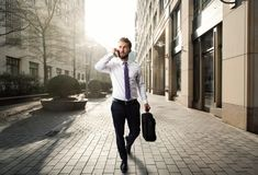 Attractive business man walks through berlin while talking on his smart phone Royalty Free Stock Images