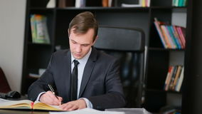 Attractive business man working with a computer and documents in the office stock footage