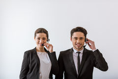 Attractive business people. Attractive businesspeople in classic suits smiling, looking at camera and talking using audio headset, on white background Stock Images