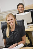 Attractive business people sitting at desks. royalty free stock image