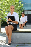 Attractive business people sitting on the street Royalty Free Stock Photo