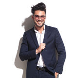 Attractive business smiling and pulling his jacket Stock Photo