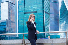 Attractive business woman on the background of skyscrapers with phone Stock Photography