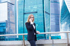 Attractive business woman on the background of skyscrapers talking on the phone Stock Photography