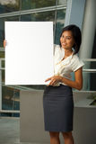 Attractive Business Woman Blank Sign Vertical. An attractive and smiling business woman holds a blank sign in front of a modern office complex.  Custom text Royalty Free Stock Images