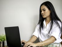 Attractive business woman in co-working space looking at labtop screen concentrate her work. Attractive beautiful asian business woman in co-working space royalty free stock photo