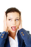 Attractive business woman covers her ears. Royalty Free Stock Image