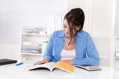 Attractive business woman at desk. Stock Photos