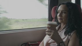 Attractive business woman enjoying trip on train commuting to work office sitting near window and drinking coffee -. Attractive business woman enjoying trip on stock footage