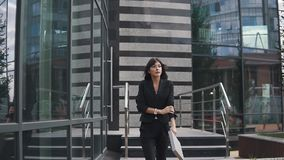 Attractive business woman exits from a modern business center and confidently walks down the street stock footage