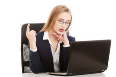 Attractive business woman in eyeglasses is sitting and pointing Stock Image