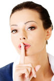 Attractive business woman with finger on lips. Royalty Free Stock Photography