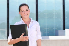 Attractive business woman with folder in the street Royalty Free Stock Image