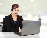 Attractive business woman with headset working on a laptop Stock Photo