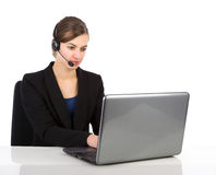 Attractive business woman with headset working on a laptop Stock Image
