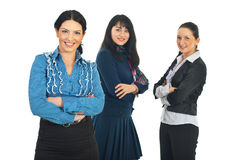 Attractive business woman and her team. Attractive business woman  standing with arms folded in front of camera and her team of women smiling in background Stock Photo