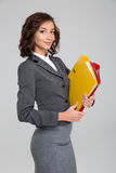 Attractive business woman holding colorful binders. Attractive happy curly smiling confident business woman in gray costume holding colorful binders with royalty free stock photos