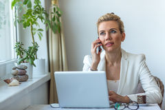 Attractive business woman in the home office working on laptop and speaks on a mobile phone. Royalty Free Stock Images