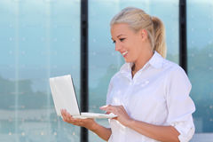 Attractive business woman with laptop in the street Stock Photography