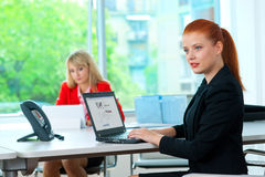 Attractive business woman in office with colleague in background Stock Photos