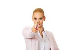 Attractive business woman pointing on camera with oversized pen Royalty Free Stock Image