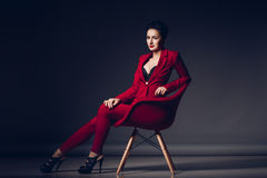 Attractive business woman. Portrait of a sexy young business lady in a red suit on a dark background.  Royalty Free Stock Photography