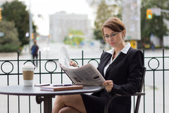 Attractive business woman reads the newspaper at outdoor cafe Stock Photo