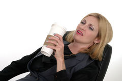 Attractive Business Woman Relaxing With Coffee. Attractive business woman relaxing at her desk with a cup of coffee in a popular but generic paper coffee cup Stock Photo