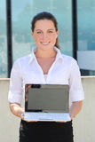 Attractive business woman showing laptop screen in the street. Young attractive business woman showing laptop screen in the street stock images