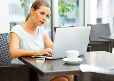 Attractive business woman sitting in a cafe with a laptop and co Stock Photos