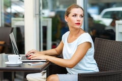 Attractive business woman sitting in a cafe with a laptop and co Stock Photography